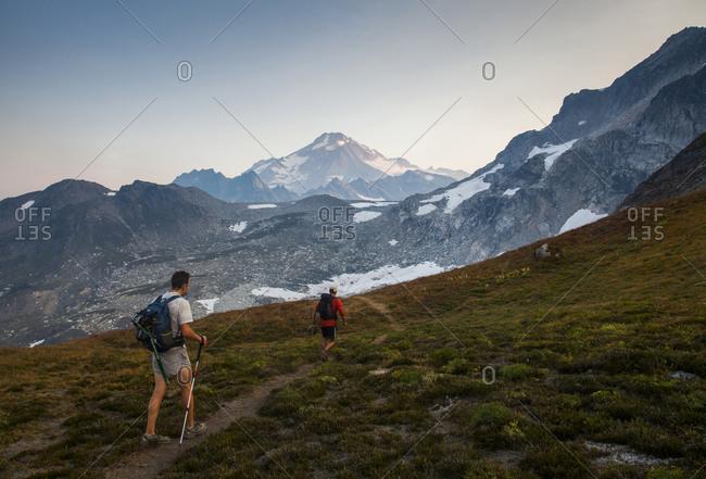 Two hikers climb towards the summit of glacier peak in Washington.