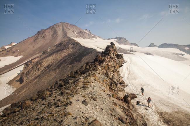 Two hikers climb towards the summit of glacier peak at dawn.