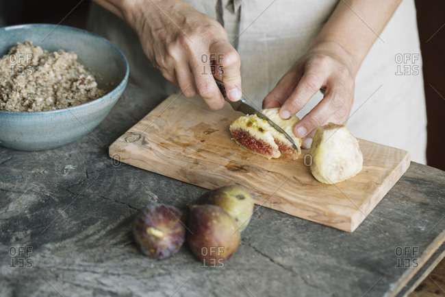 Woman cutting fresh figs on cutting board