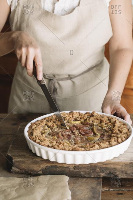 Woman cutting homemade figs pie
