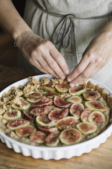 Woman decorating homemade figs tart