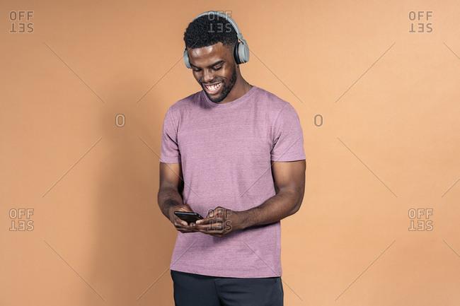Handsome black man wearing headphones and looking at his phone in studio against brown background