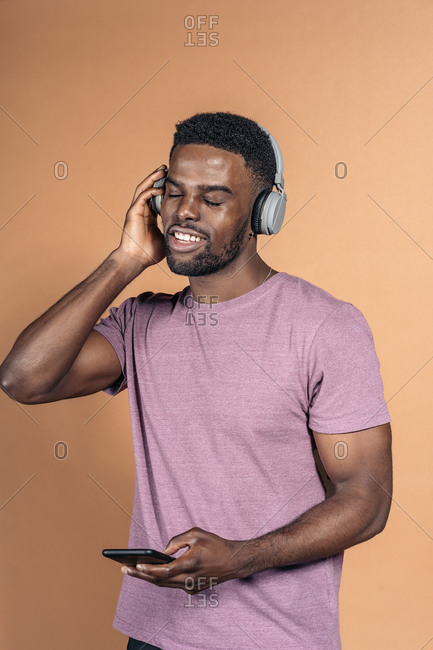 Happy black man wearing headphones and using his phone with eyes closed in studio against brown background