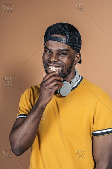 Handsome black man wearing headphones looking at camera in studio against brown background