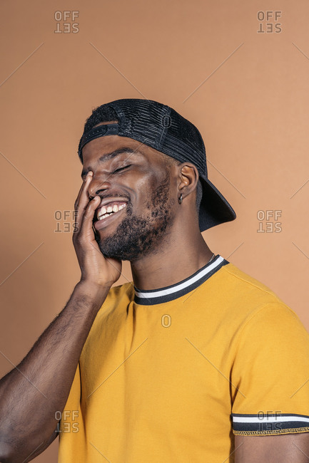 Handsome young black man in studio laughing and having fun in front of brown background