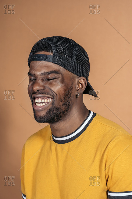 Handsome black man in studio laughing and having fun in front of brown background