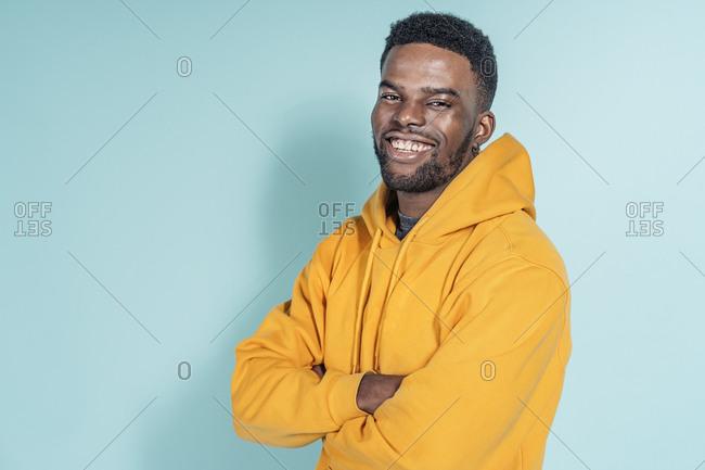 Happy young black man wearing hoodie posing in studio against blue background