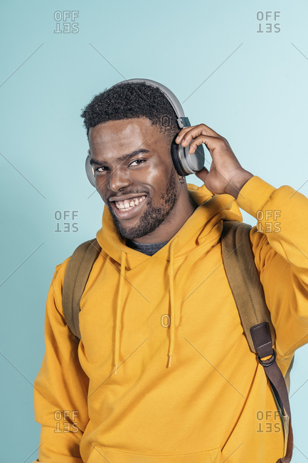 Handsome African young man listening to music and looking at camera in studio shot