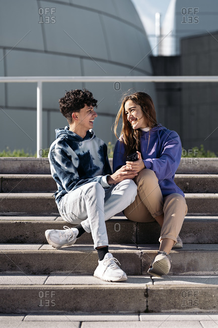 Happy teen friends sitting on stairs and using mobile phone