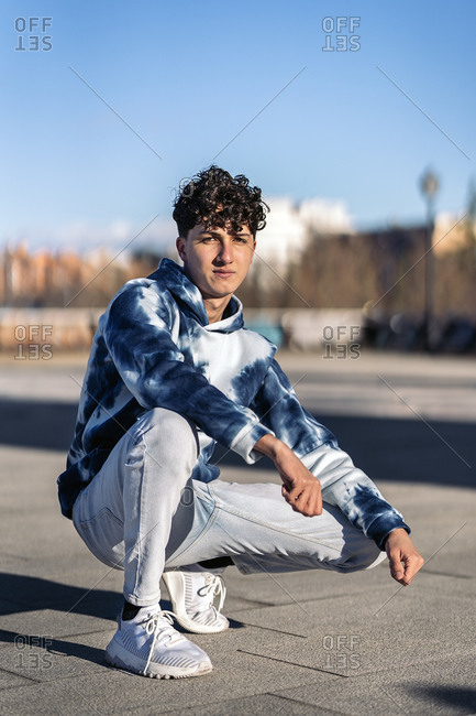 Serious boy wearing urban clothes posing and looking at camera