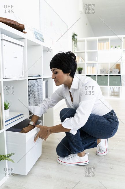 Businesswoman organizing shelves at the office