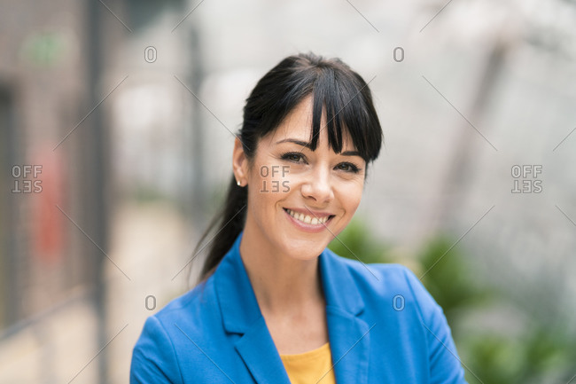 Smiling businesswoman with bangs posing outdoors