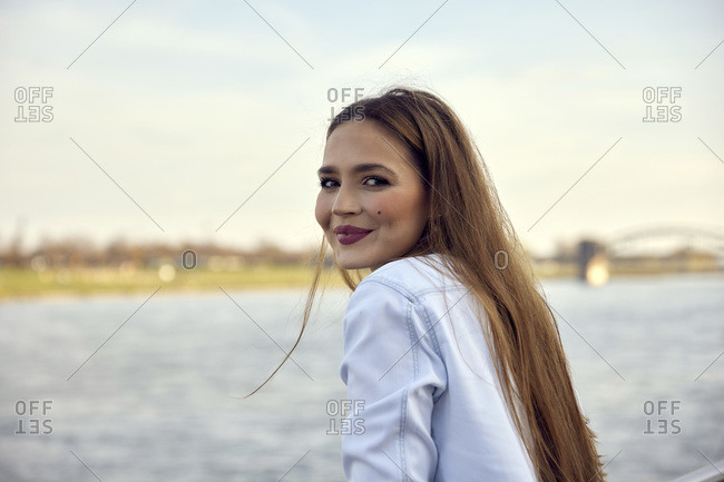 Smiling businesswoman standing against sky