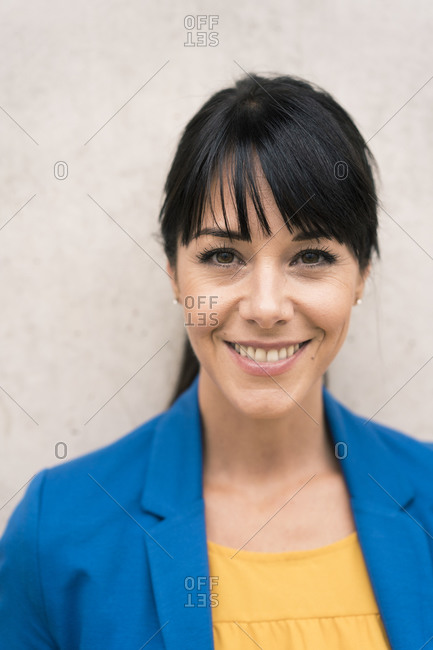 Mature businesswoman smiling against wall