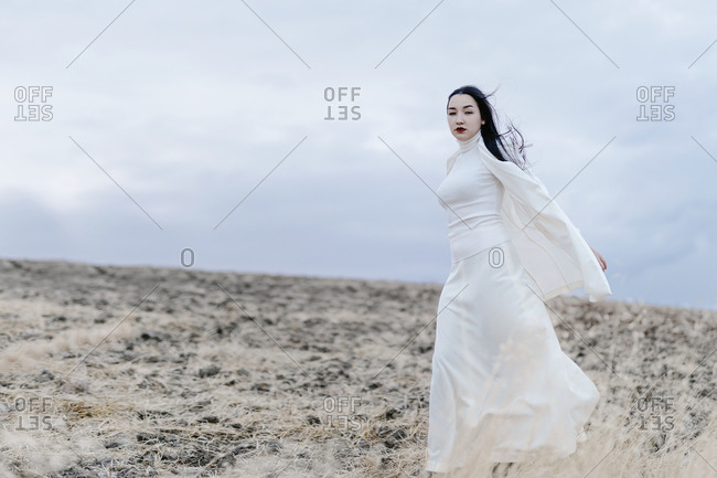 Fashionable woman walking against sky
