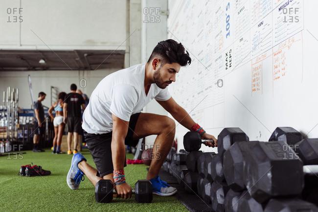 Athlete taking dumbbells at gym