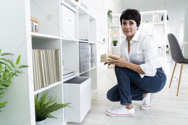 Portrait of businesswoman organizing office shelves