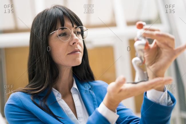 Mature businesswoman analyzing model in office