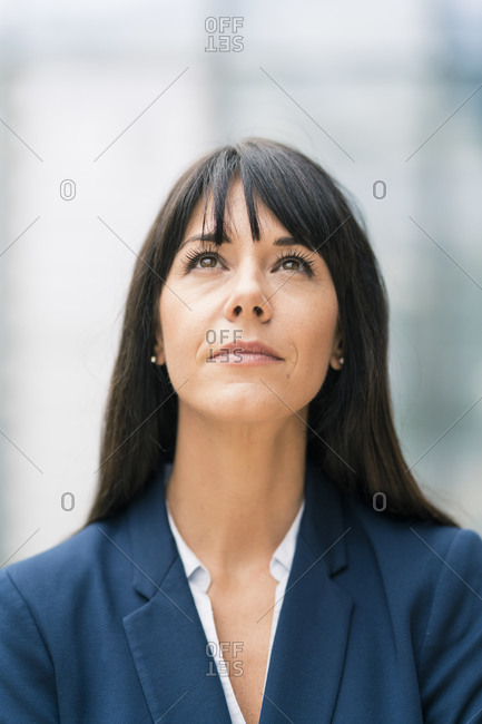 Thoughtful businesswoman with bangs looking up