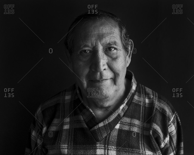 Smiling senior man against black background