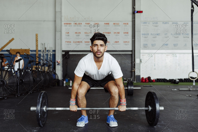 Young man practicing weightlifting at gym