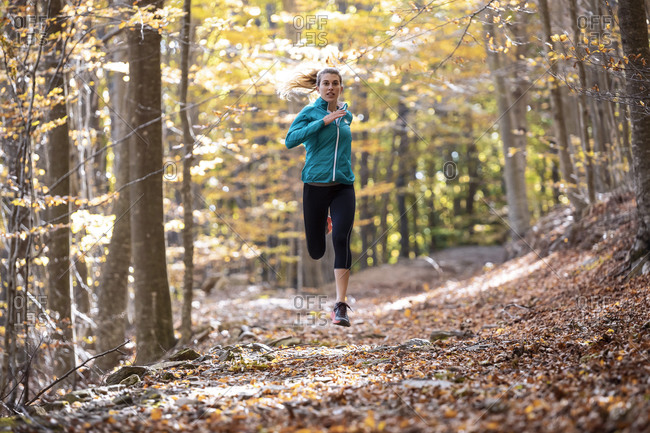 Young sportswoman running on forest path