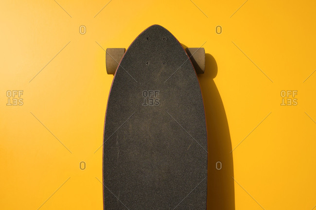 Black longboard leaning on yellow wall
