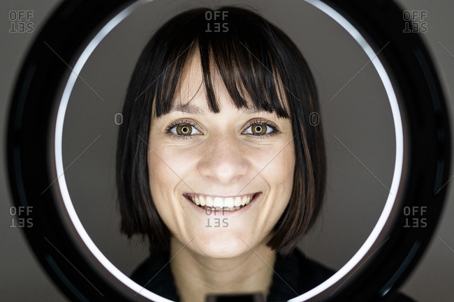 Smiling young woman with ring light