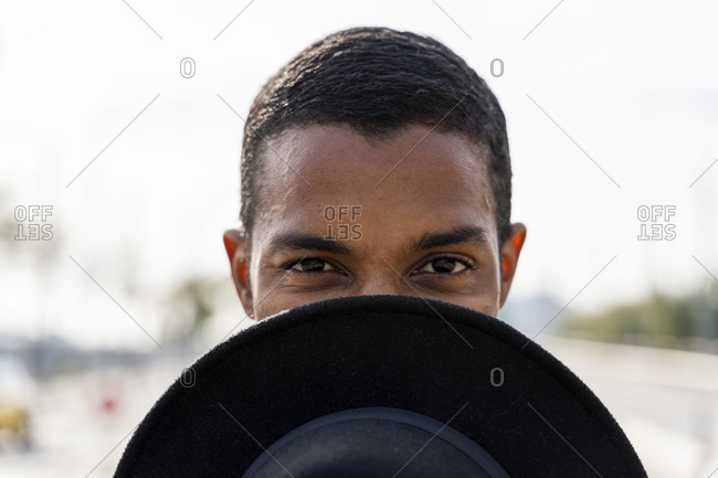 Young man covering face with hat