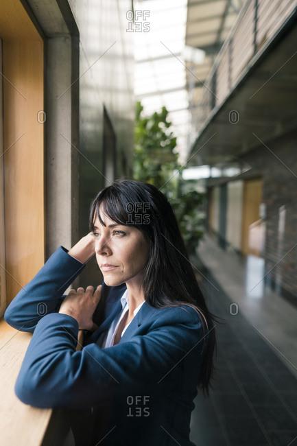 Thoughtful businesswoman leaning on window in corridor
