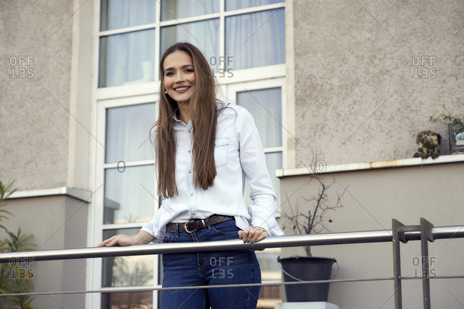 Young businesswoman smiling while standing in balcony