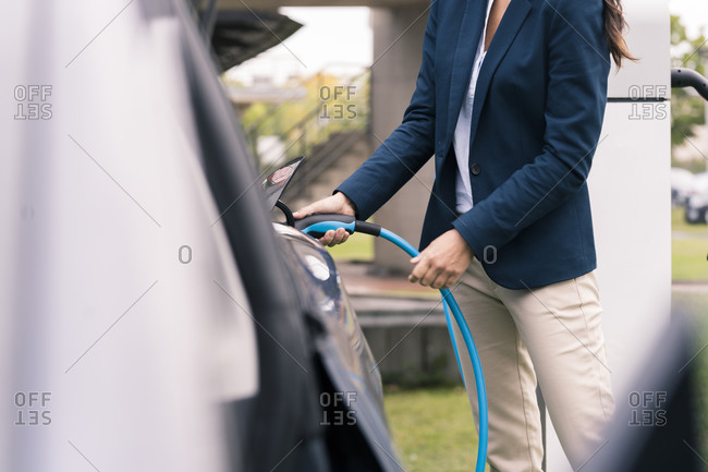 Mature businesswoman charging electric car at Station