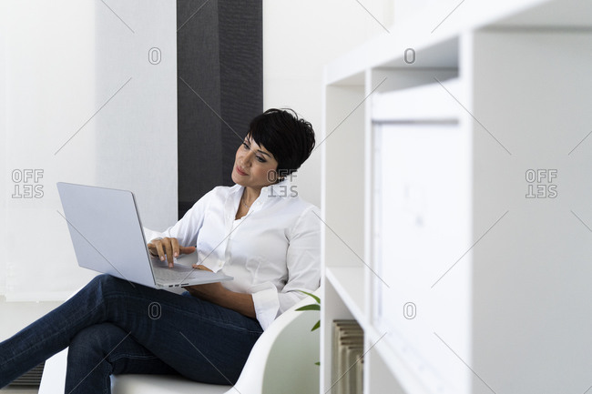 Businesswoman sitting in office armchair with laptop