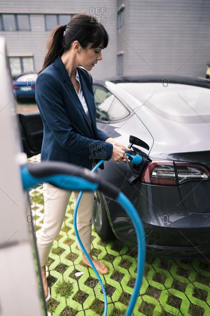 Female entrepreneur charging electric car at station