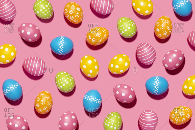 Handmade decorated Easter eggs on pink background