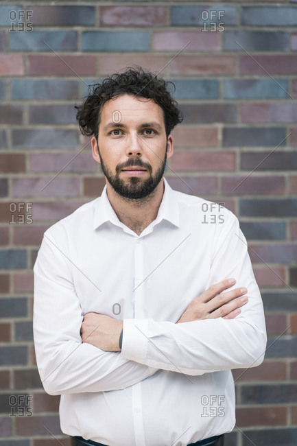 Male entrepreneur with arms crossed against wall