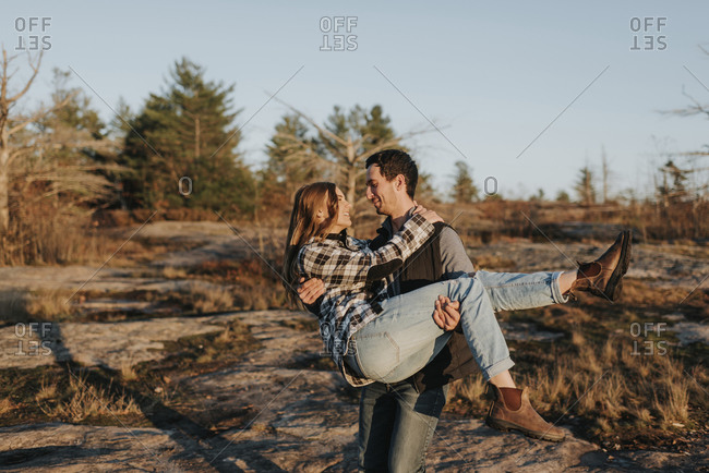 Young man carrying girlfriend during autumn hike
