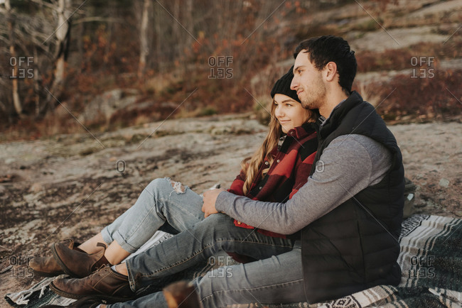Young couple sitting together during autumn hike