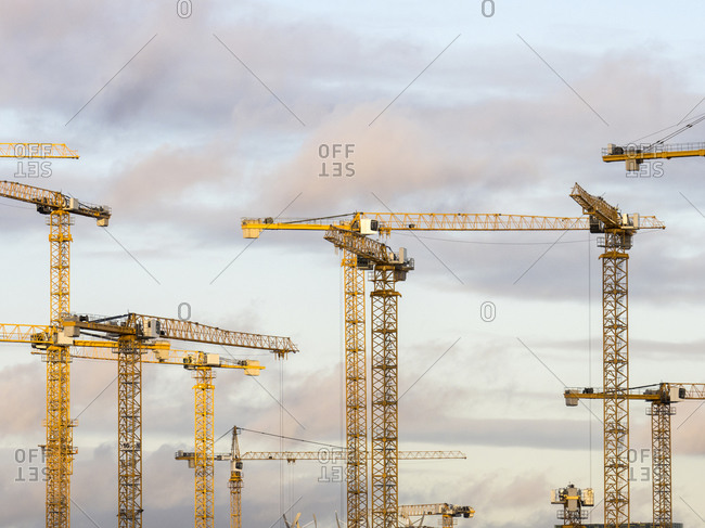 Construction cranes standing against sky at dusk
