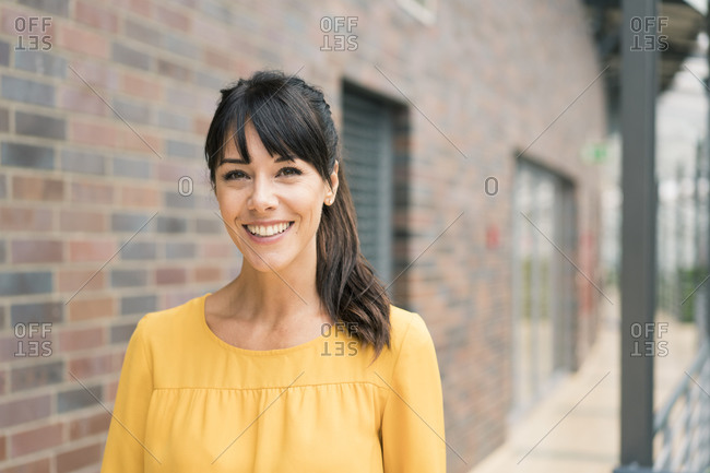 Smiling female entrepreneur by wall in corridor