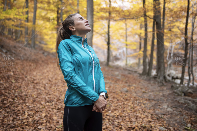 Sportswoman looking up while standing in forest