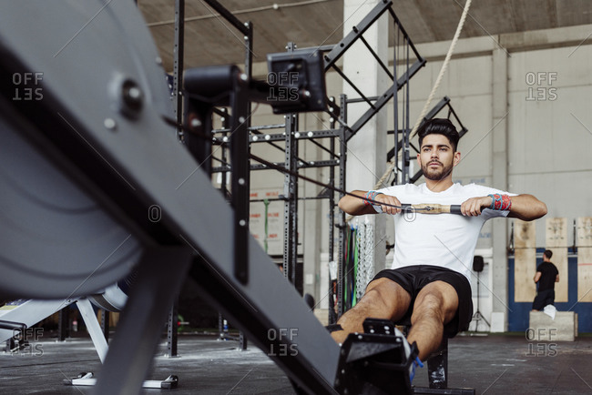 Sportsman exercising with rowing machine at gym