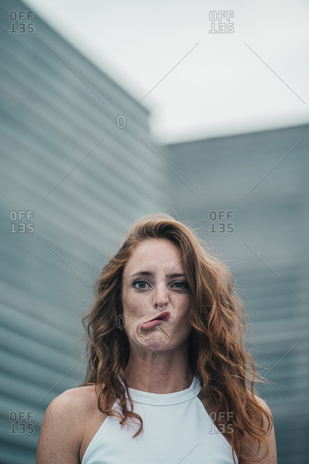 Young woman making face while standing outdoors