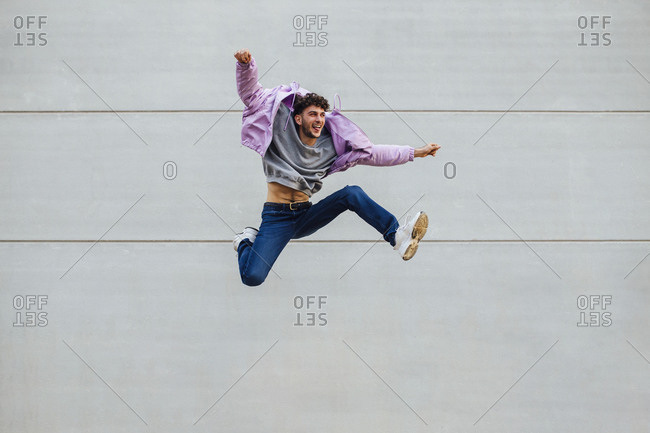 Cheerful man jumping happily against gray wall
