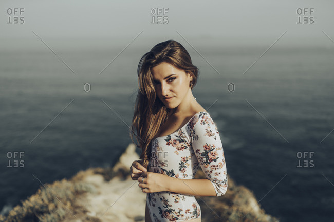 Young woman staring while standing against sea