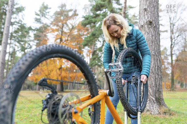 Blond woman repairing bicycle at Cannock Chase