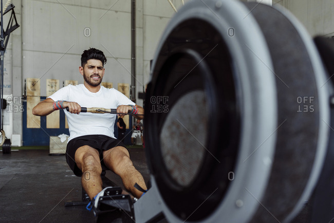 Athlete exercising with rowing machine at gym