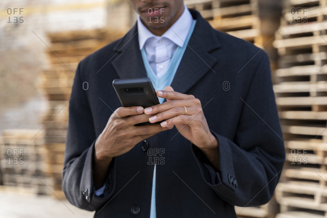 Young man using mobile phone against pallets