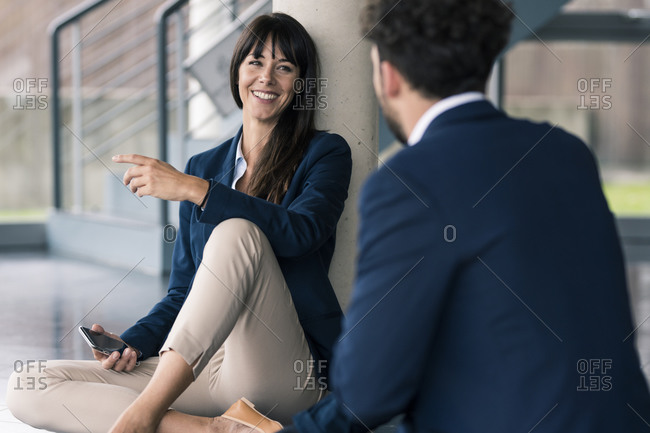 Colleagues sitting on floor in office lobby