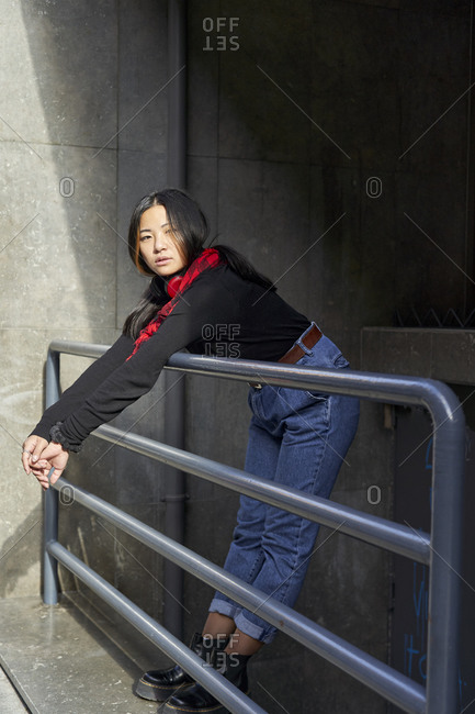 Woman looking away while leaning on railing